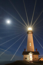 Low Angle View Of Illuminated Lighthouse Against Sky At Night