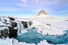 Scenic View Of Frozen Waterfall And Kirkjufell Mountain