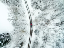 Aerial View Of Car Driving On Road Passing Through Snowy Landscape