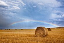 Scenic View Of Rainbow Over Field With Hay Bales