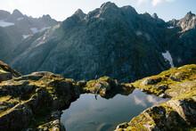 Woman Hiking On Ridge By Mountains