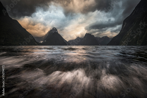 Scenic view of storm clouds over mountains and fjord - 376794172
