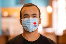 Indoor Portrait Of A Hispanic Male Wearing A Mask And An I Voted Today Sticker On The Mask
