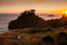 Tent On Coastline By Pacific Ocean During Sunset