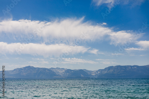 Clouds Across a Blue Sky with Mountains and a Lake