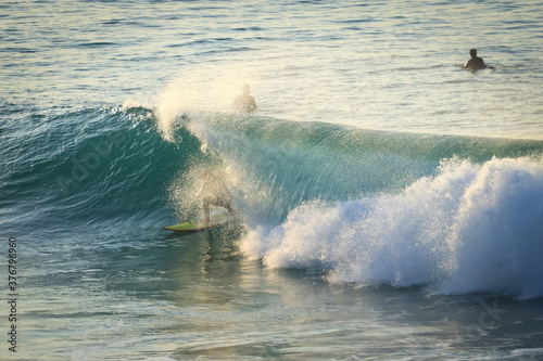 Surfer on Ocean Wave Getting Barreled at Sunset