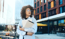 Front View Photo Of A Modern It Woman With Curly Hair And Eyeglasses Posing In The City With A Tablet And Laptop While Waiting For Somebody