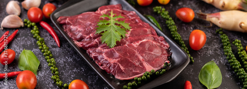 Fotografia Sliced ​​raw pork used for cooking with chili, tomato, basil, and fresh pepper seeds