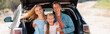 Panoramic shot of family looking at camera while sitting in car trunk outdoors