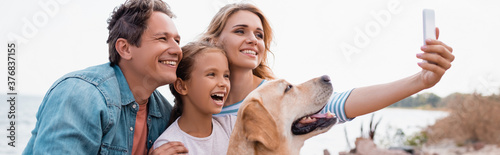 Canvas Print Horizontal image of family with golden retriever taking selfie on beach