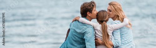 Horizontal crop of parents kissing daughter near sea Fototapet