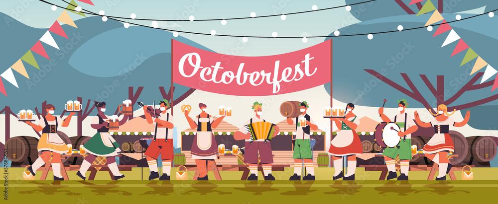 Fototapeta mix race people in face masks drinking beer and having fun Oktoberfest festival celebration concept landscape background full length horizontal vector illustration