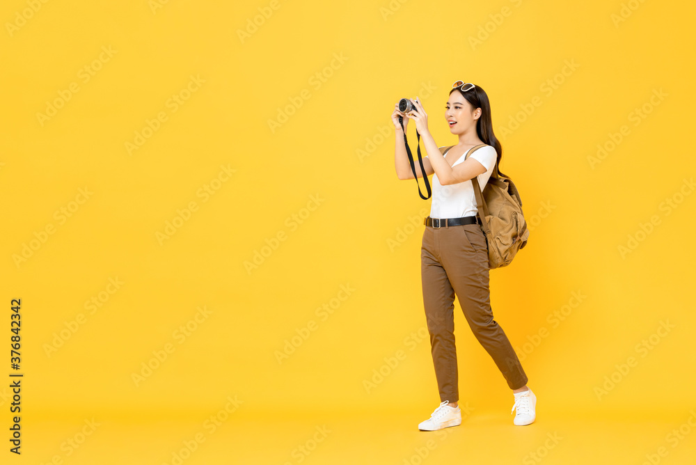 Fototapeta Young Asian tourist woman taking photo with camera isolated on yellow background