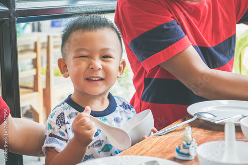 Happy little Asian boy tucking into his lunch and learning to feed himself with family at the restaurant Fototapet
