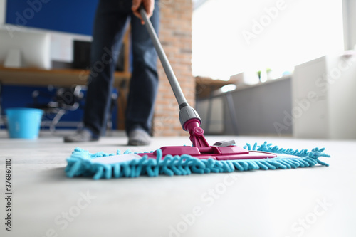 Obraz na płótnie Man with mop washes floor in office