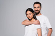 bearded man in white t-shirt embracing young asian woman while posing isolated on grey