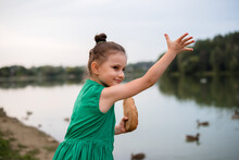 Little Girl 5 Years Old In A Beautiful Green Dress Feeds The Ducks With Bread On The River Bank