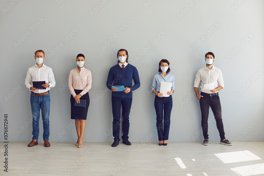 Fototapeta Job seekers in face masks waiting for job interview standing in corridor keeping safe distance