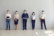 Leinwandbild Motiv Job seekers in face masks waiting for job interview standing in corridor keeping safe distance