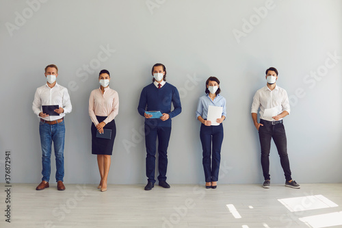 Job seekers in face masks waiting for job interview standing in corridor keeping safe distance
