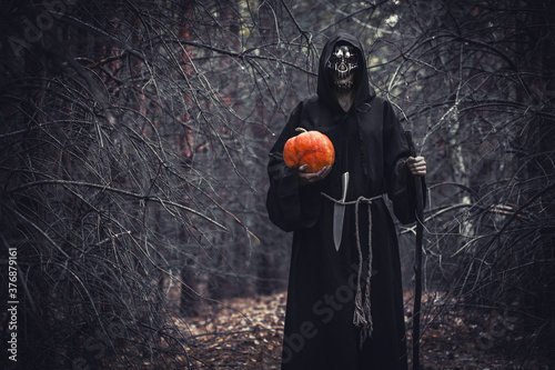 Photo Woman devil ghost demon costume horror and scary she holding pumpkin in hand in the forest