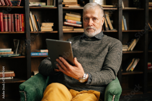 Fotografia Portrait of confident bearded gray-haired mature adult male holding digital tablet in hand sitting at chair at home on background of bookshelves in cozy room with an authentic aristocratic interior