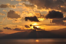 Sunset Over The Sea And Mountain With Sun Rays Passing Through Clouds