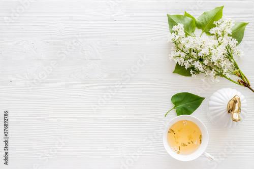 Fototapeta Flat lay of jasmine flowers bouquet with cup tea on workspace obraz na płótnie