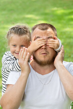 Family Time. Father And Daughter Together. The Little Girl Covered Her Father's Eyes With Her Hands. Wondering Man