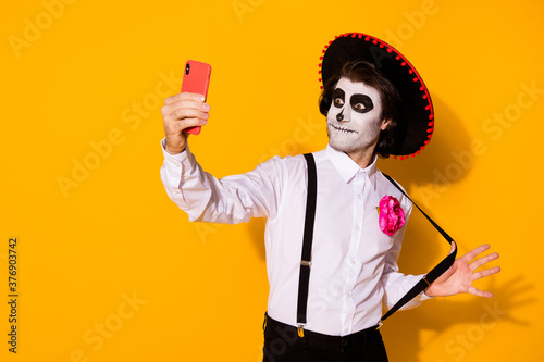 Portrait of his he nice handsome painted spooky guy caballero taking making selfie calavera celebration look outfit having fun isolated bright vivid shine vibrant yellow color background