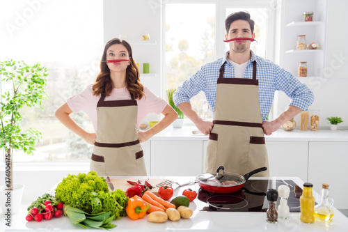 Fotografie, Tablou Two funny people enjoy hobby cooking have red hot chilli pepper nose imagine fak