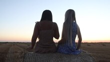 Girls Take Selfie On A Stack Of Straw At Sunset