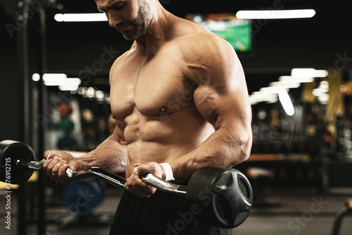 Foto Muscular bodybuilder doing biceps curls with a barbell in the gym