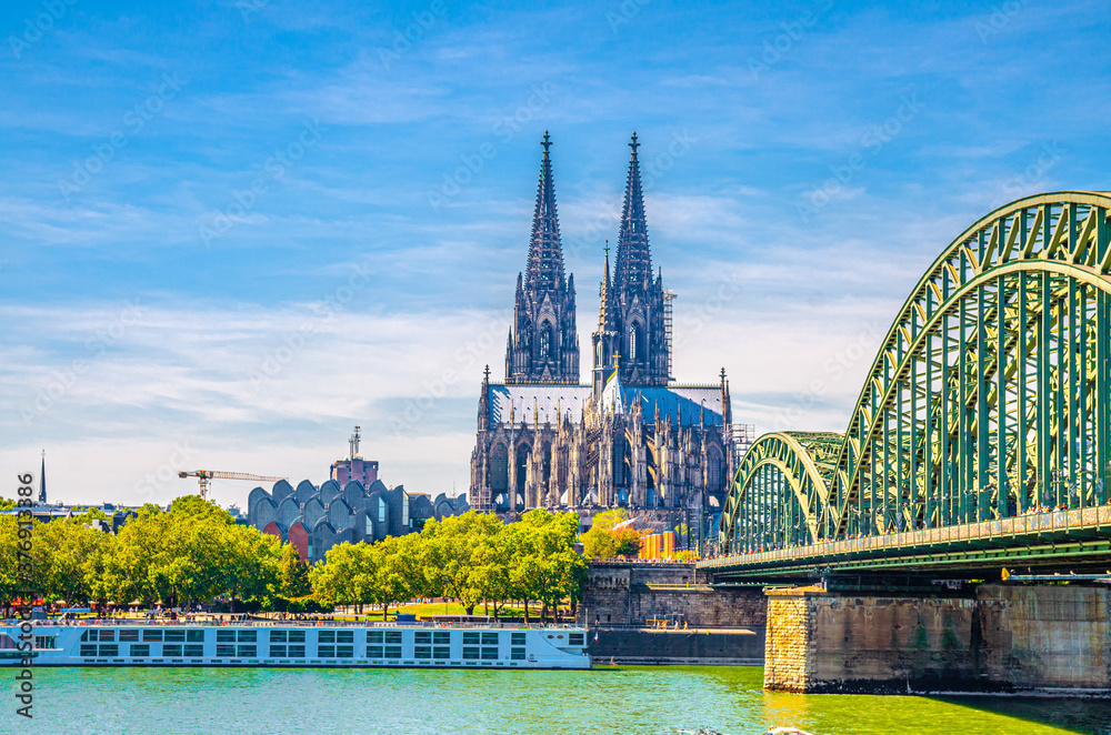 Fototapeta Cologne cityscape of historical city centre with Cologne Cathedral Roman Catholic Church of Saint Peter gothic style building, Hohenzollern Bridge across Rhine river, North Rhine-Westphalia, Germany