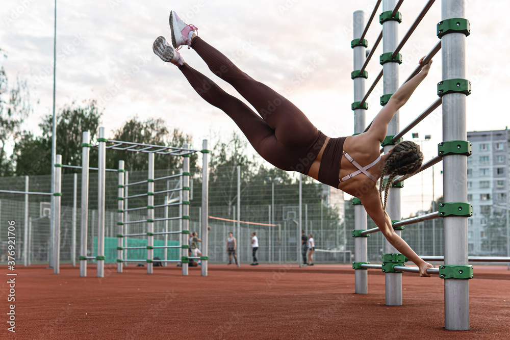 Fototapeta Strong woman is doing human flag exercise during her calisthenics workout