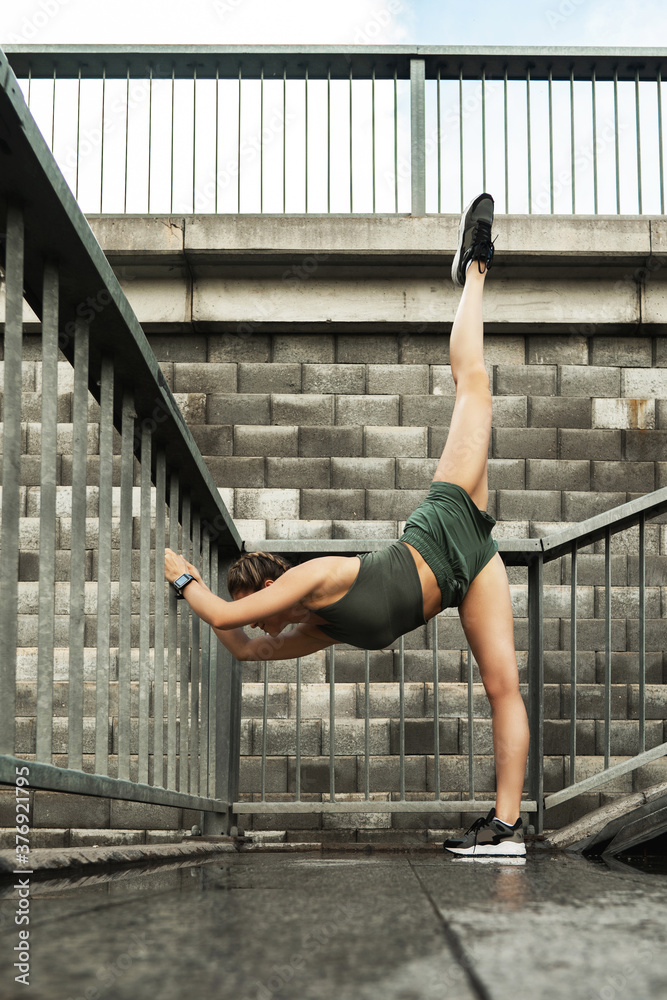 Fototapeta Sportive woman is stretching during fitness workout on a street