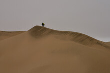 Two Hikers Cresting A Dune In ...