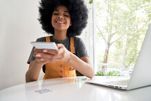 Smiling African American Young Hipster Mixed Race Gen Z Young Woman With Afro Hair Holding Smart Phone Scanning QR-code On Cafe Table To Read Menu Or Make Mobile Payment In Cellphone App Concept.