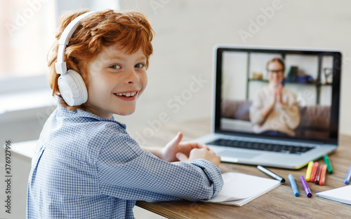Cheerful boy during online lesson at home. Fototapeta
