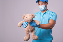 Young Delivery Man With A Teddy Bear Is Wearing Prevention Mask And Gloves