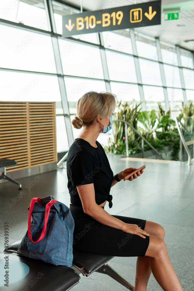 Fototapeta Young woman is a wearing prevention mask in an airport during flight awaiting