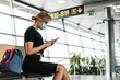 Leinwandbild Motiv Young woman is a wearing prevention mask in an airport during flight awaiting