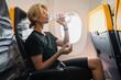 Leinwandbild Motiv Woman drinks water during her flight in an airplane