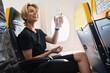 Leinwandbild Motiv Young woman drinks water during her flight in an airplane