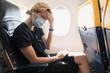 Leinwandbild Motiv Woman wearing prevention mask during a flight inside an airplane