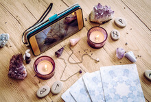 Spiritual Session, Fortune Telling Live Video Through Smartphone Concept. Various Magical Objects By Phone. Candles Burning.
