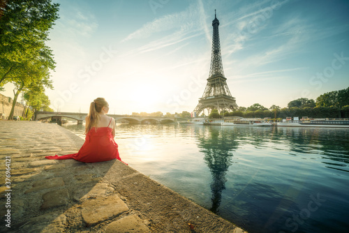 Obraz na płótnie Young woman in red, looking to Eiffel tower, Paris