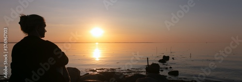 Foto silhouette of mourning woman by the sea at sunset, loss, farewell, sympathy