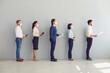 Leinwandbild Motiv Job seekers wearing face masks standing in row keeping safe distance while waiting for job interview