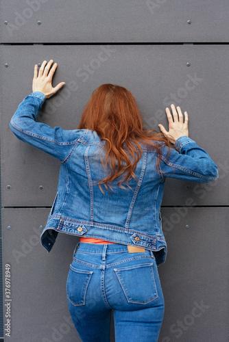 Leinwand Poster Redhead woman pushing against a grey wall